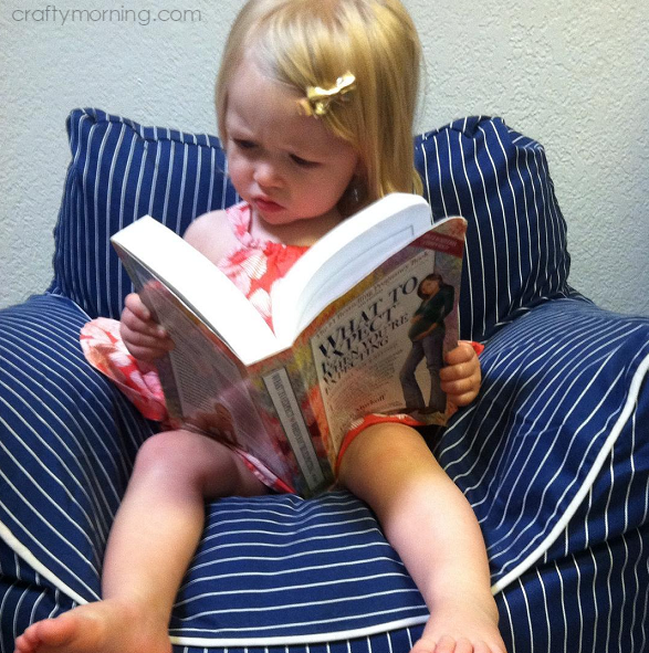 little-girl-reading-what-to-expect-pregnancy-announcement